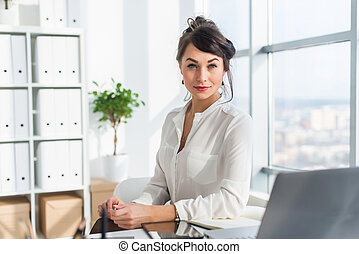 Close-up portrait of a woman sitting in modern loft office,...