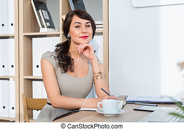 Beautiful female office worker sitting on workplace,...