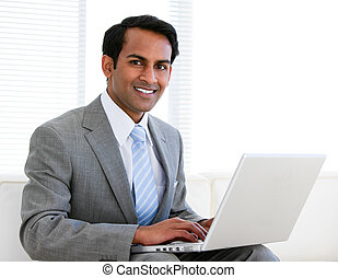 Confident businessman working on his computer in the office