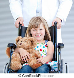 Portrait of a little girl sitting on the wheelchair supported by a male doctor at the hospital