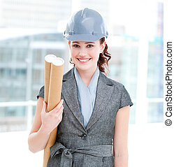 Portrait of a self-assured female architect holding blueprints