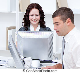 Self-assured young business people working at computers in...