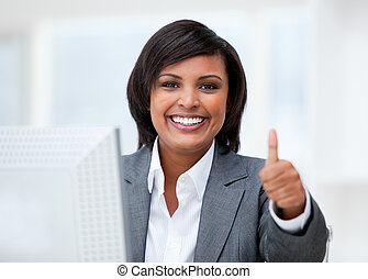 Happy businesswoman with a thumb up working at a computer in...