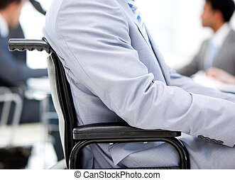 Close-up of a businessman sitting on a wheelchair in a...