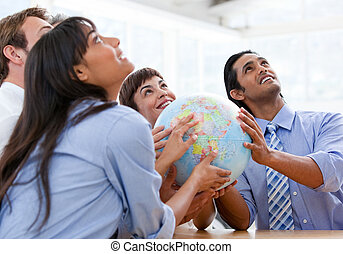 International business team holding a terrestrial globe in a...