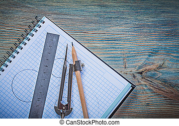 Checked copybook ruler drawing compass pencil on vintage wooden