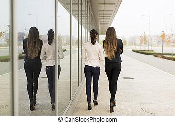 Two women walking - Rear view of two women walking on the...