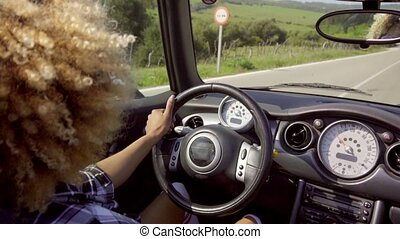 Young woman driving her cabriolet with the top down and the...
