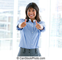 Successful female executive with thumbs up standing in the...