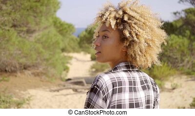 Woman in Plaid Shirt Walking on Sand near Coast - Waist Up...