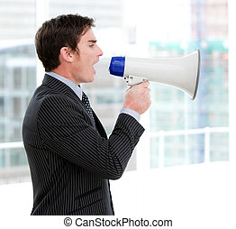 Frustrated businessman yelling through a megaphone standing...