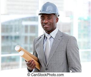 Portrait of a charismatic male architect holding blueprints...