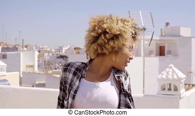 Young Woman with Afro Relaxing on Urban Rooftop - Waist Up...