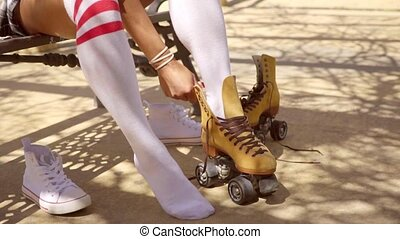 Girl Put On Roller Skates - Young woman in white socks put...