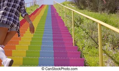 Young Woman Walks Down The Colorful Stairs - Attractive...