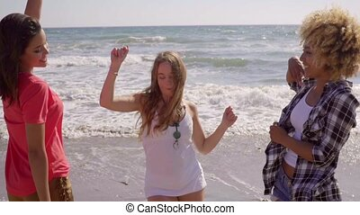 Young People On The Beach - Three young sexy girlfriends hop...