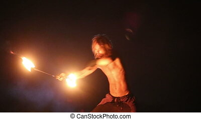 Male Artist of spins fire poi on rock at night on background...