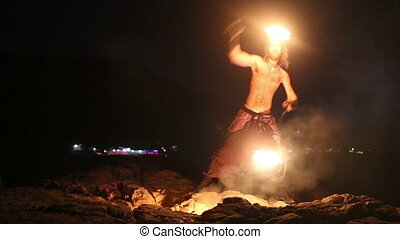 Male Artist of spins fire poi on rock at night