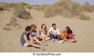Group of young multiracial friends playing guitar