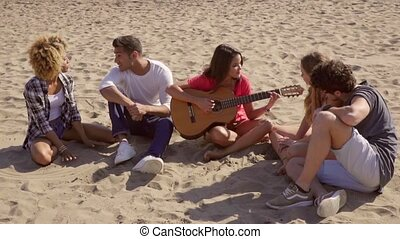 Young woman playing guitar to her friends as they sit around...