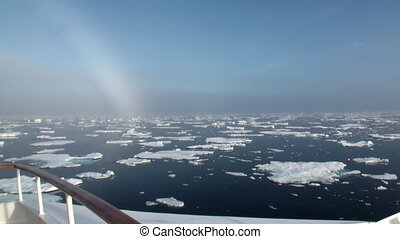 Rainbow in ocean among icebergs and ice in Arctic - Rainbow...