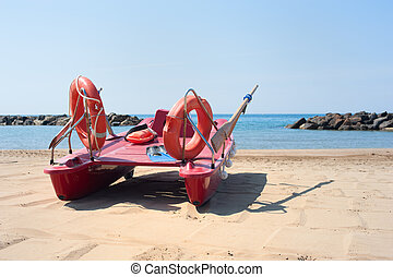 Lifeboat on empty beach in summer day