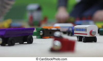 wooden vagons on toy railway background of playing children defocused