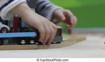 boy playing with toy wooden railway - close up of boy hands...