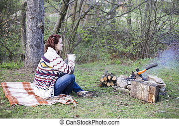 A girl sits by the fire and drink coffee - Girl sitting near...