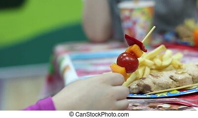 close up of girl eating vegetables on a skewer background of...