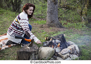 A girl sits by the fire and drink coffee. - Girl sitting...