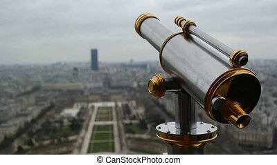 Sightseeing telescope on Eiffel Tower, Paris, France. View of Paris from the upper balcony in the spring March day
