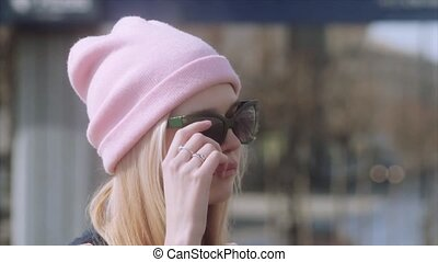 Cute young girl takes off sunglasses and puts it in his...