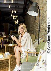 Woman with a phone sitting in a cafe