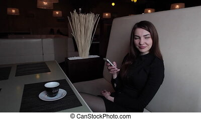 the girl in the cafe communicate in social networks on your phone