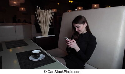 the girl in the cafe communicate in social networks on your...