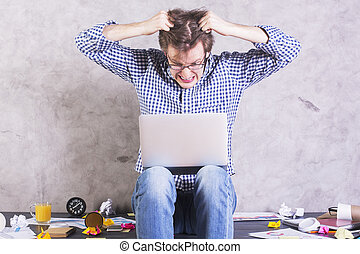 Man pulling hair - Crazy furious man with laptop sitting on...