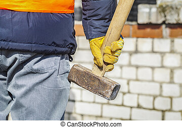 Worker with sledgehammer near to brick wall