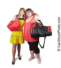 girls with travelling bags - Two happy casual girls with...