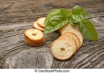 Mini rolls of baked bread and basil isolated on wooden...