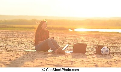 Girl on a beach talking on the phone at sunset - Girl on a...