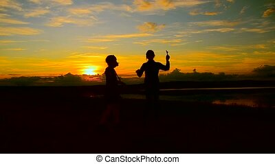 Girls dancing on the background of beautiful fiery sunset