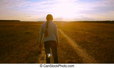 Girl against the sunset is on the road and looking back laughing