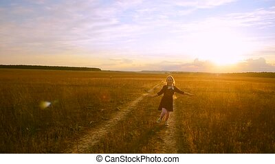 Cheerful girl at sunset on the road running