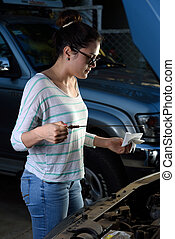 girl checking oil level - girl checking the oil level of her...