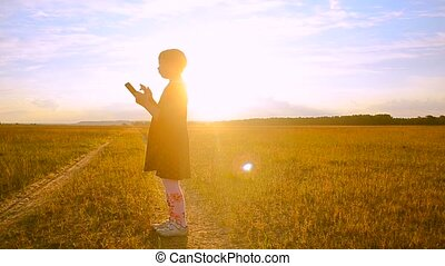 Girl on the sunset background with the tablet is scratched