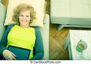 Woman relaxing with a Tablet PC on the sofa