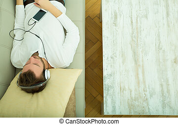 Young man listening to music on the sofa - A young man lying...