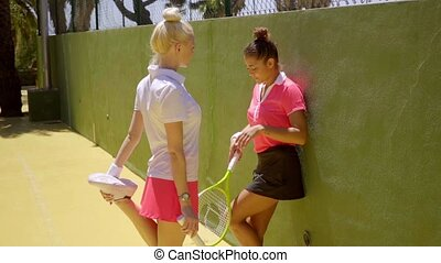 Two sporty young women tennis players standing talking in...