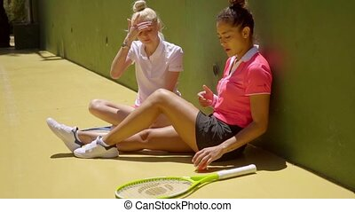 Two sporty young tennis friends sitting relaxing in the sun...